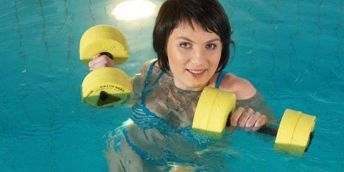 Женщина с гантелями в бассейне